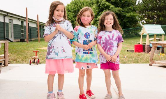 Three school agers wearing tie-dye shirts